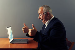 Man looking at graph and showing thumbs up. Happy senior businessman looking at graph and showing thumbs up Royalty Free Stock Photo