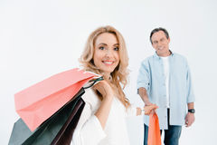 Man looking at happy blonde woman holding shopping bags stock image
