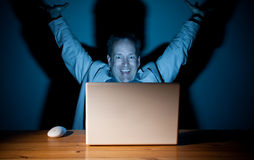 Happy computer guy. Man looking happy in front of his computer Royalty Free Stock Photos