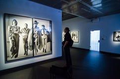 Man looking at Helmut Newton's work 'Sie Kommen' Stock Images