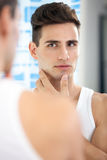 Man looking at himself in mirror Stock Photography