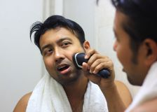 Man looking after his appearance in front of a mirror beauty styling lifestyleman lookingIndian asian after his appearance in fron. Man lookingIndian asian after Royalty Free Stock Image