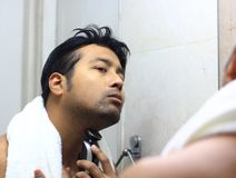Man looking after his appearance in front of a mirror beauty styling lifestyleman lookingIndian asian after his appearance in fron. Man lookingIndian asian after Stock Image