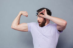 Man looking at his biceps with delight. Potrait of a man looking at his biceps with delight over gray background royalty free stock image