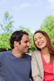 Man looking his friend as she is laughing joyfully while sitting Stock Photos