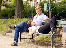 Man Looking at His Girlfriend Resting on His Lap. Sitting guy on a bench looking at his girlfriend resting on his lap Stock Photography