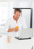Man looking at his laptop. While he is drinking oranje juice Stock Images