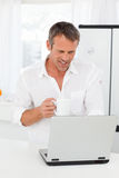 Man looking at his laptop while he is drinking Royalty Free Stock Images