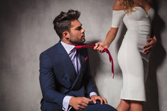 Man looking at his lover while she  pulls his tie Royalty Free Stock Images