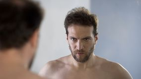 Man looking at his mirror reflection with hatred and shame, feeling guilty. Stock photo stock photo