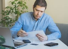 Man looking at his monthly bills. Man looking at his monthly bills at home Royalty Free Stock Images