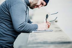 Man looking at his notebook and writing something - close up shot Stock Image