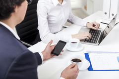 Man looking at his phone, woman typing in the office Royalty Free Stock Photo
