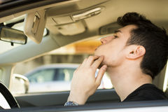 Man Looking at his Pimple Using Mirror of a Car. Close up Handsome Young Man Looking at his Pimple on his Face Using a Mirror Inside his Car royalty free stock image
