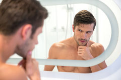 Man looking at his reflection in the mirror Stock Photography