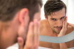 Man looking at his reflection in the mirror. Portrait of a happy man looking at his reflection in the mirror in bathroom Royalty Free Stock Photos