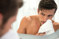 Man looking at his reflection in the mirror. Portrait of a man with towel looking at his reflection in the mirror in bathroom Royalty Free Stock Photography