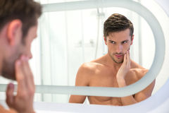 Man looking at his reflection in the mirror. Portrait of a young man looking at his reflection in the mirror in bathroom Royalty Free Stock Photo