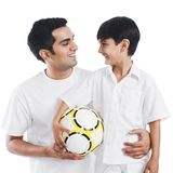 Man looking at his son and smiling. Man holding soccer ball and smiling with his son Royalty Free Stock Image