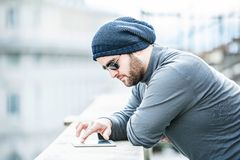Man looking at his tablet and scrolling with hand. Man with grey top, hat and glasses is looking at his tablet and scrolling, browsing social media Royalty Free Stock Image
