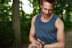 Man Looking at his Watch While in Outdoor Training. Half Body Shot of an Athletic Young Man Checking at his Wrist Watch While in an Outdoor Training at the Park Stock Photography