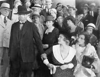 Man looking at his wife in anger while a group of people is watching. (All persons depicted are no longer living and no estate exists. Supplier grants that stock images