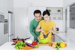Man looking at his wife makes salad Stock Image
