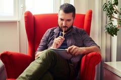 Man looking at his writing pad Stock Photography