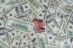 Man looking through a hole between dollar bills Stock Image