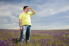 Man looking at the horizon. Young man in a field looking at the horizon Stock Photos