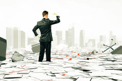 Man is looking at the horizont among pile of papers and. Businessman is looking at the horizont among pile of papers and office stuff Stock Photos