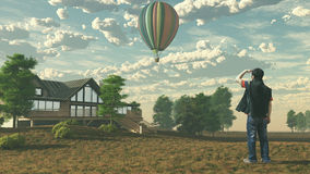 The man is looking at the hot air balloon Stock Images