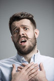 Man is looking imploring over gray background Royalty Free Stock Images
