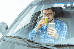 Man looking info in phone while sitting in car Royalty Free Stock Photography