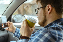 Man looking info in phone while sitting in car Royalty Free Stock Image