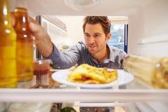 Man Looking Inside Fridge Full Of Unhealthy Food� Royalty Free Stock Photos
