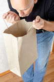 Man Looking Inside a Paper Bag Royalty Free Stock Photography