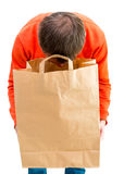 Man looking inside paper bag. Stock Images