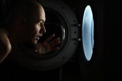 Man looking inside washing machine Royalty Free Stock Images