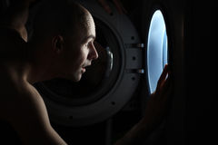 Man looking inside washing machine Stock Photo