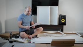 Man is looking on an instructions for assembly of furniture, holding hammer, then turning book and smiling to camera. Crazy angry man is looking on an stock video footage
