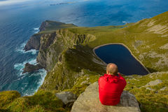Man looking at a lake in a hill on Achill island, Co. Mayo. Man looking at a lake in a hill on Achill island, Co. Mayo, Ireland stock photography