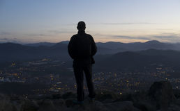 Man looking at the landscape at sunset. Stock Image