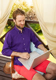 Man looking at laptop computer outdoor on garden terrace Royalty Free Stock Photos