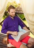 Man looking at laptop computer outdoor on garden terrace Royalty Free Stock Photos