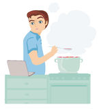 Man looking in laptop during cooking soup at home kitchen Royalty Free Stock Images