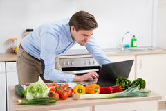 Man Looking On Laptop In Kitchen Royalty Free Stock Photography