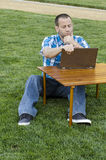 Man looking at a laptop outdoors. Man looking at a laptop outdoors sitting at a picnic table, debating his next move and a pathway behind him Royalty Free Stock Photography