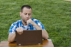 Man looking at a laptop outdoors. Man looking at a laptop outdoors sitting at a picnic table in the grass Stock Photo