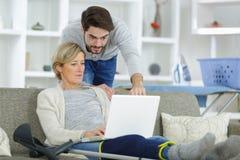 Man looking at laptop over shoulder injured woman. Man looking at laptop over shoulder of injured woman Stock Photo